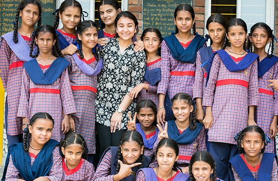 Gayatri Malhotra, Milken SPH '19 (in flower print) with students at a government school in Punjab.