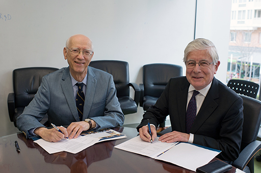 Reg Mitchell (left) and Dean Dolling sign scholarship agreement.