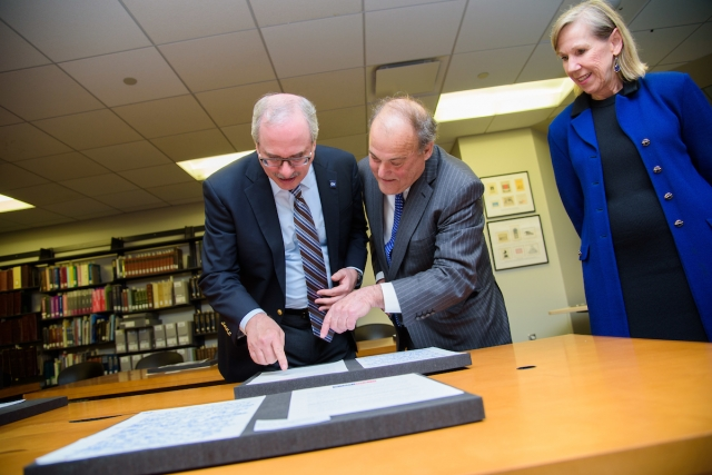 GW President Thomas LeBlanc, Mark Plotkin, and Geneva Henry, dean of GW Libraries and Academic Innovation examine the collection