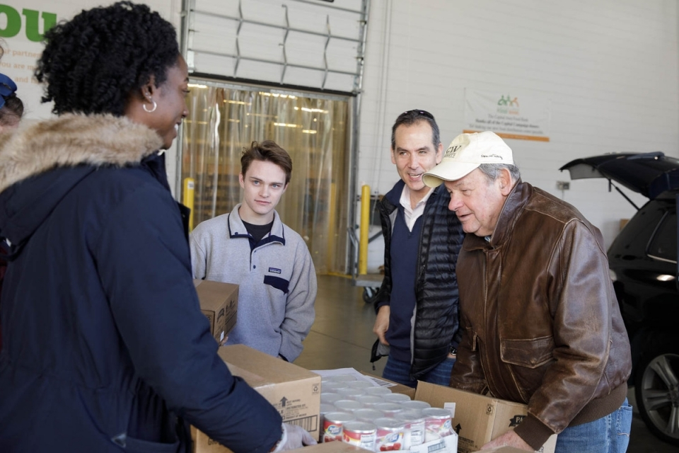 Steven V. Roberts (r) helps student volunteers to load canned food supplies into the Store's vans during a resupply run.