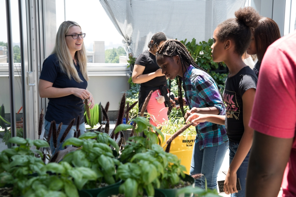Greenhouse manager Rachel Klein with students from Washington Middle School for Girls
