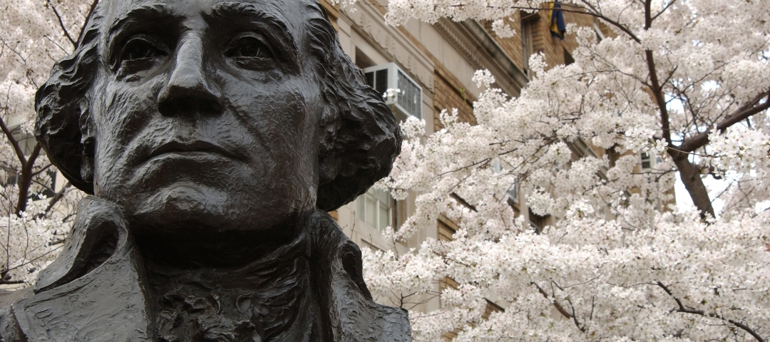 Bust of George Washington in spring at the corner of campus, with cherry blossoms around it.