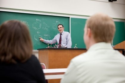 Professor Michael King shown at a blackboard demonstrating organic chemistry to a class.